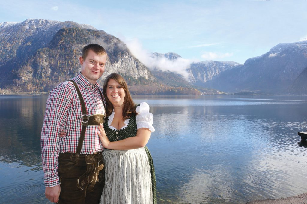Emily with husband wearing traditional Austrian dress in front of landscape